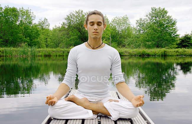 Человек медитирует на деревянном пирсе — стоковое фото