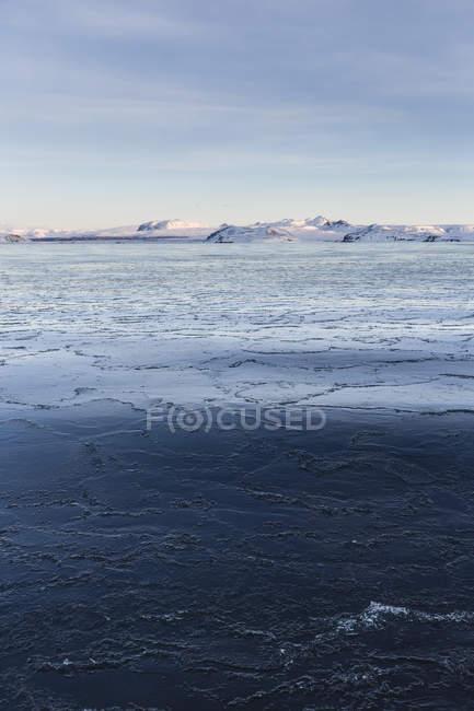 Vista panorâmica da costa gelada e distantes montanhas cobertas de neve, Islândia — Fotografia de Stock