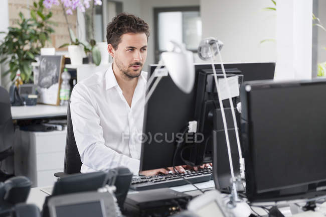 Young man using computer in office interior — Stock Photo