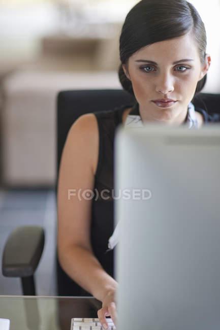 Jeune employé de bureau utilisant un ordinateur — Photo de stock