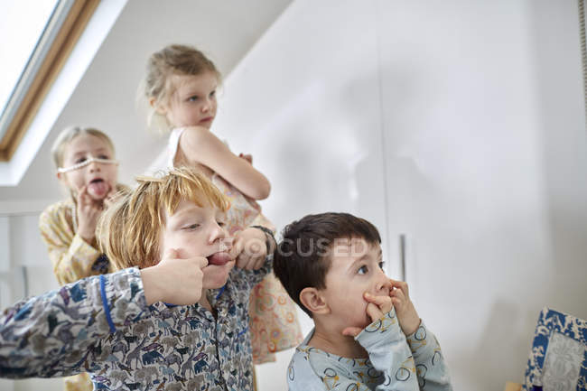 Children making faces in loft room — Stock Photo