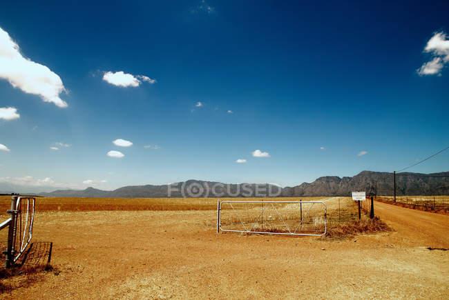 Cerca en el paisaje rural seco con cielo azul vivo - foto de stock