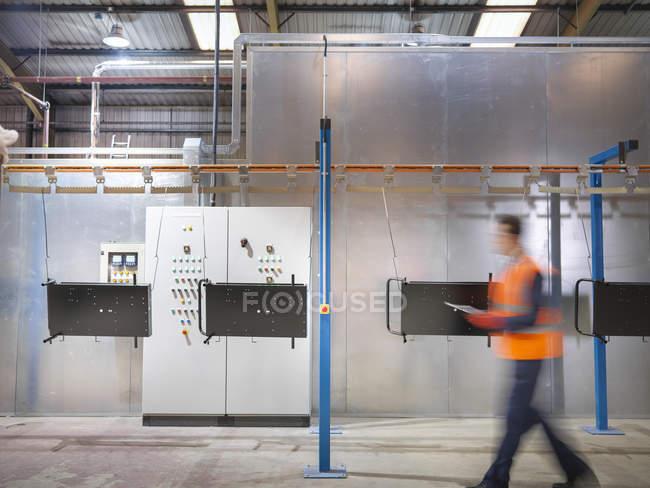 Arbeiter mit Klemmbrett läuft in Blechfabrik an Farbsprühmaschine vorbei — Stockfoto