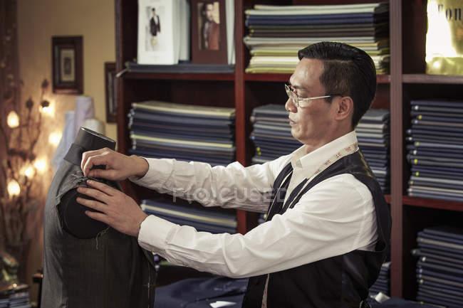 Alfaiate de fixação do vestuário em alfaiates manequim na loja — Fotografia de Stock