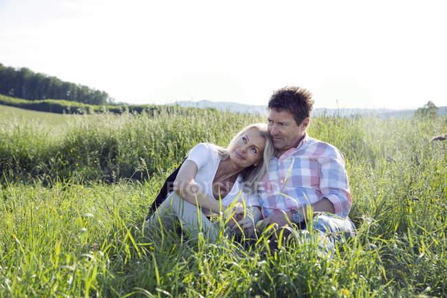 Зрелая пара, сидящая в поле — стоковое фото