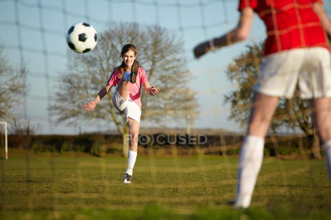 Mädchen kickt Fußballball ins Tor — Stockfoto