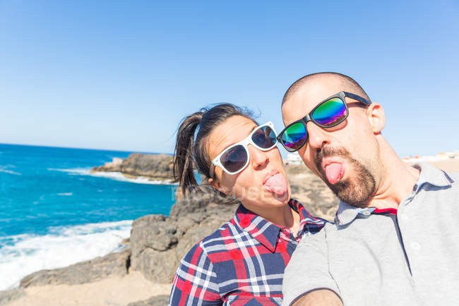 Молода пара вирізняє мови для смартфонів, Ель - Котільо, Фуертевентура (Іспанія). — стокове фото