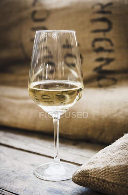 Bicchiere di vino bianco su legno con sacco — Foto stock