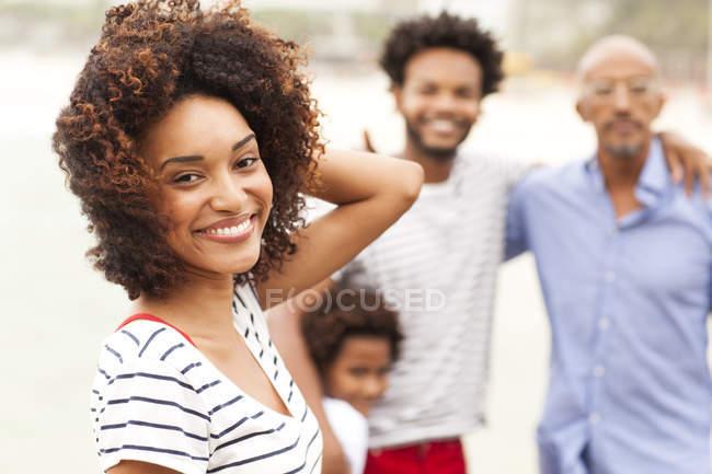Retrato de mujer joven y familia en la playa de Ipanema, Río de Janeiro, Brasil - foto de stock
