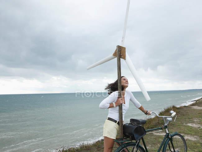 Femme avec éolienne au bord de la mer — Photo de stock