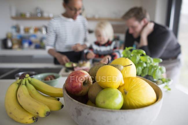 Заделывают чаши с свежие фрукты на столе с семьей на фоне — стоковое фото