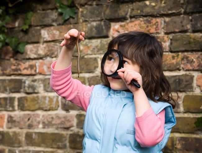 Chica mirando gusano con lupa - foto de stock