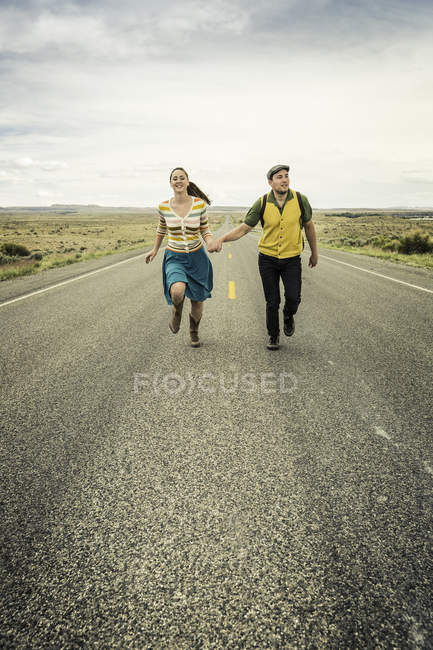 Retro style young  couple running hand in hand on road, Cody, Wyoming, USA — Stock Photo