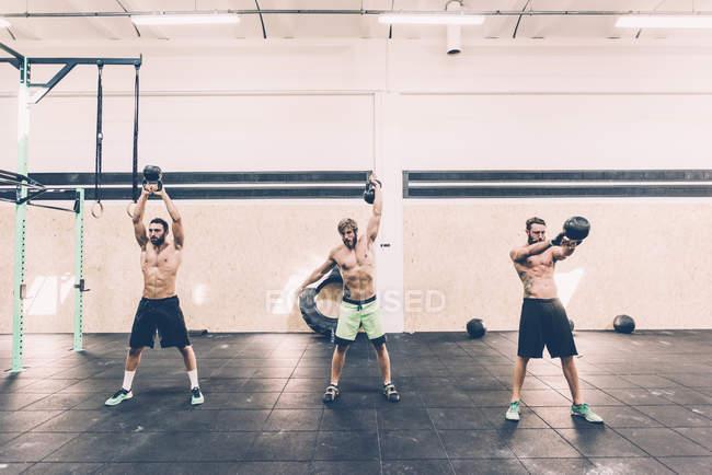 Três jovens treinadores cruzados do sexo masculino treinando com kettlebells no ginásio — Fotografia de Stock