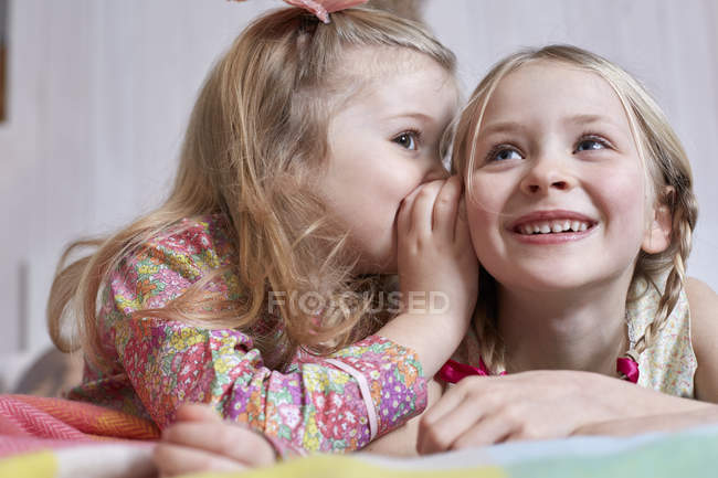 Girl whispering into sister's ear — Stock Photo