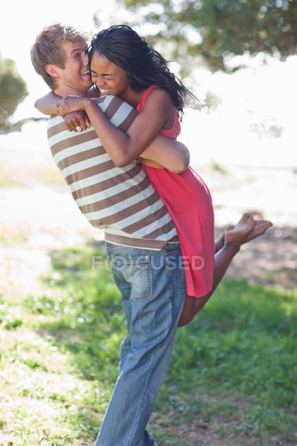 Мужчина поднимает девушку на улицу — стоковое фото
