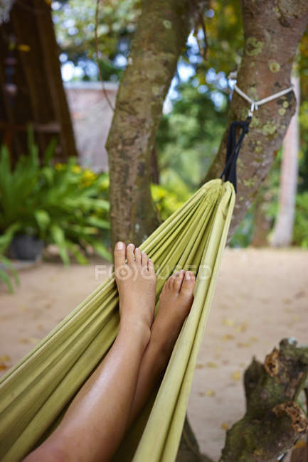 Close up of female legs and feet in beach hammock — Stock Photo