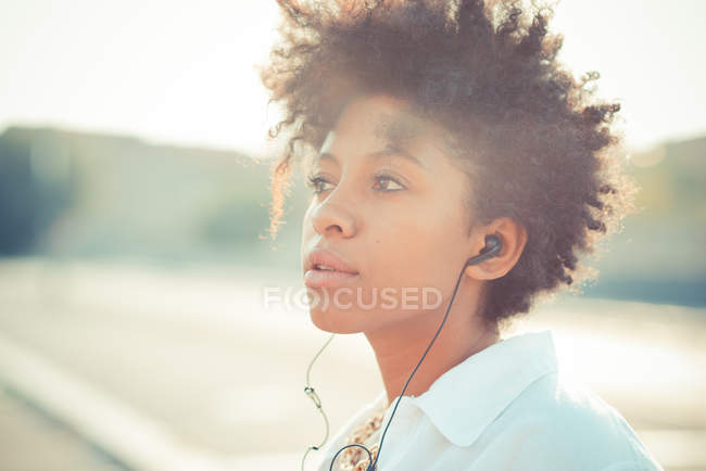 Portrait of pensive young woman listening to earphones — Stock Photo