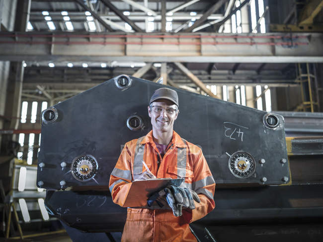 Portrait of engineer holding clipboard in factory — Stock Photo