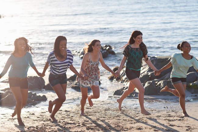 Женщины держатся за руки на пляже — стоковое фото