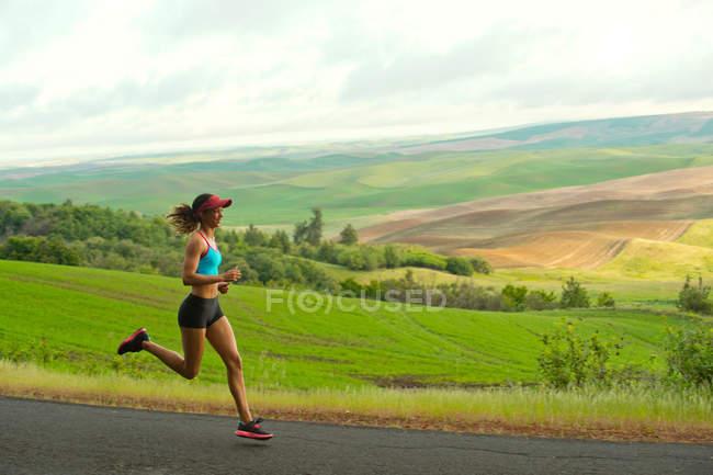Молодая женщина, бегущая в пейзаже Палхаус Хиллс, Вашингтон, США — стоковое фото