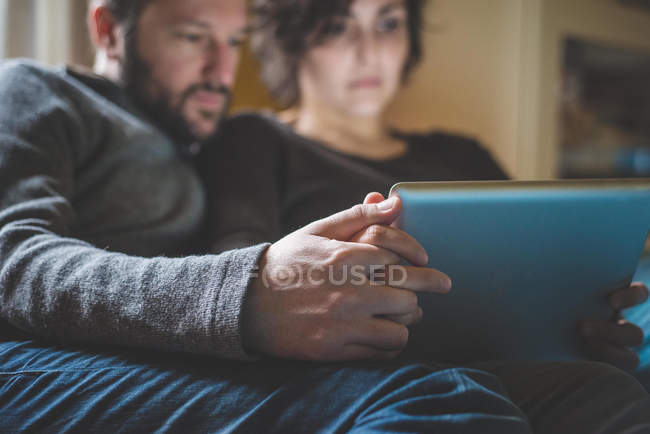 Couple sitting on sofa, looking at digital tablet — Stock Photo