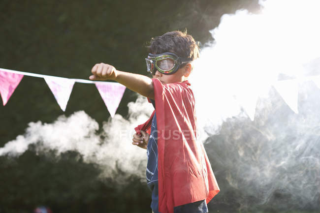 Boy wearing goggles and cape in superhero stance in front of smoke cloud — Stock Photo