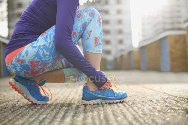 Vue recadrée de femme pliant pour attacher le lacet de chaussure de formation sportive — Photo de stock