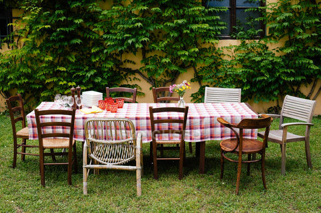 Tabelle mit karierten Tischdecken und Stühle im Garten — Stockfoto