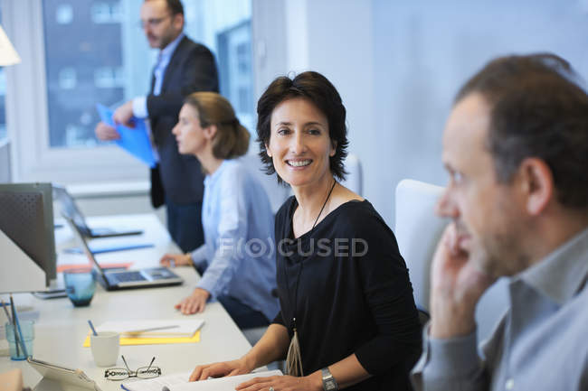 Male and female businesspeople sitting at desk in office — Stock Photo