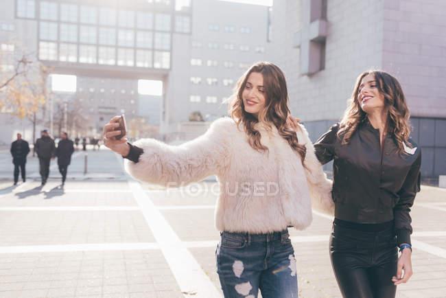 Hermanas gemelas, caminando al aire libre, tomando selfie, usando smartphone - foto de stock