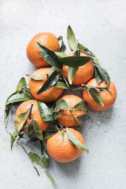 Top view of fresh tangerines with leaves on kitchen counter — Stock Photo