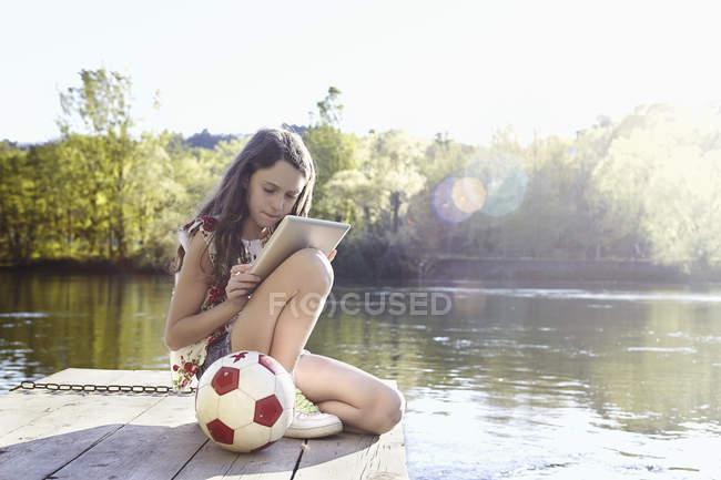 Дівчинка-підліток з м'ячем з використанням цифрової таблетки на дерев'яній пристані — стокове фото