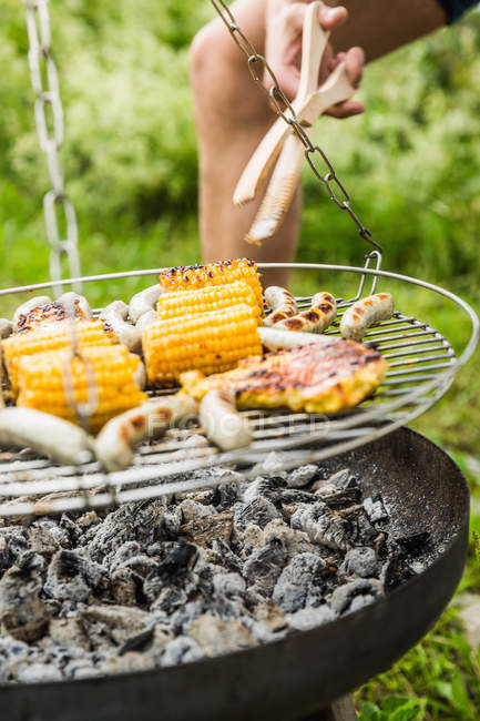 Close up partial view of young man barbecuing lunch — Stock Photo