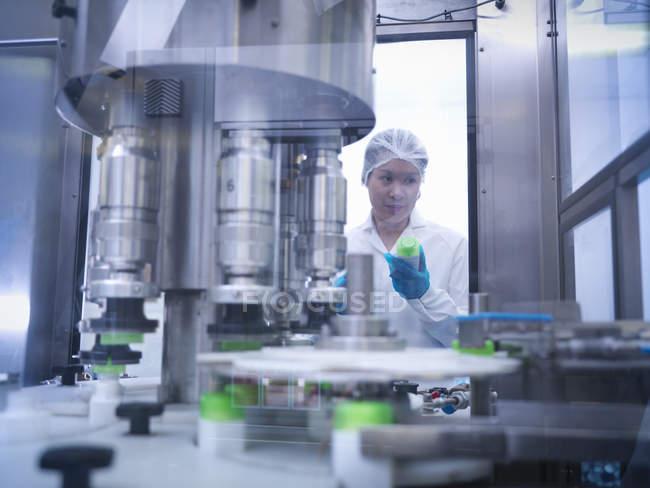 Travailleur inspectant les produits sur la chaîne de production dans l'usine pharmaceutique — Photo de stock