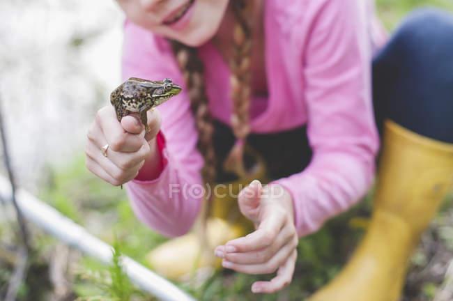 Обрезанный снимок девушки, держащей лягушку — стоковое фото