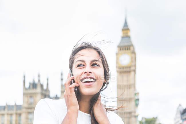Молодая женщина, использующая смартфон, здания парламента и Биг-Бен на заднем плане, Лондон, Англия — стоковое фото