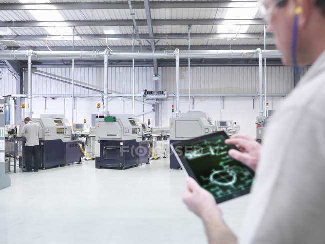 Ingénieur utilisant une tablette numérique par ligne de production en usine, gros plan — Photo de stock