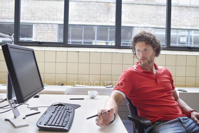 Portrait of man gazing at office desk — Stock Photo