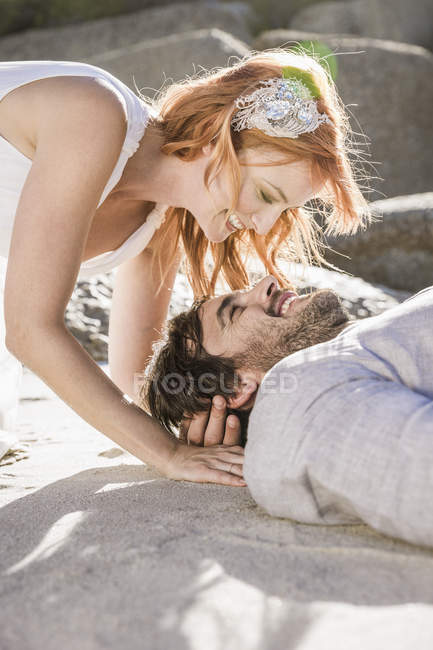 Head and shoulders of couple lying on beach face to face smiling — Stock Photo