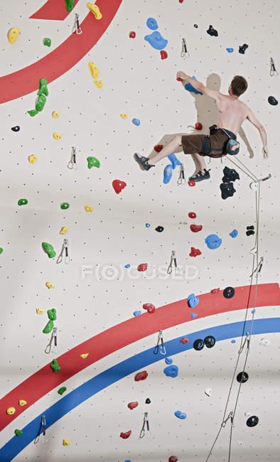 Середині дорослої людини сходження мотузками на скелелазіння стіна — стокове фото