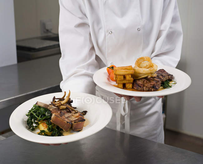 Chef holding two plated dinners of meat with vegetables — Stock Photo