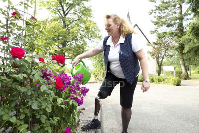 Середині дорослу жінку з протез, в саду поливу рослин — стокове фото