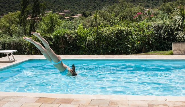Young woman diving into swimming pool, Capoterra, Sardinia, Italy — Stock Photo