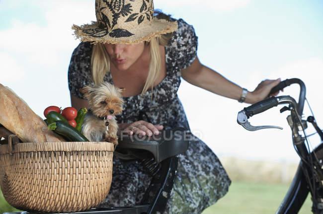 Зрілі жінки на електричних велосипеда з собакою і овочі в кошик — стокове фото