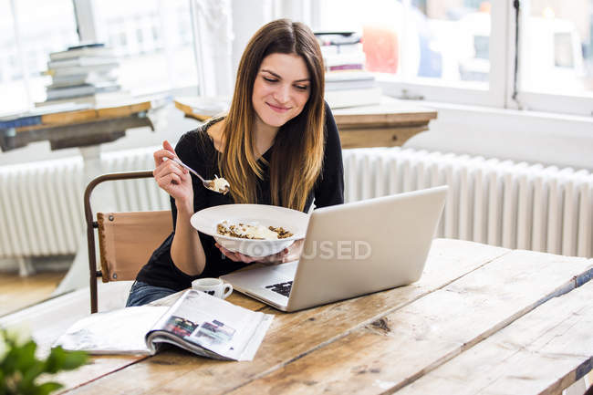 Young woman in city apartment eating muesli breakfast whilst reading  laptop — Stock Photo
