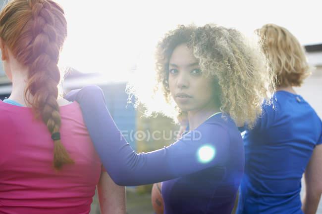 Vue arrière de trois femmes faisant de l'exercice avec une femme regardant la caméra — Photo de stock