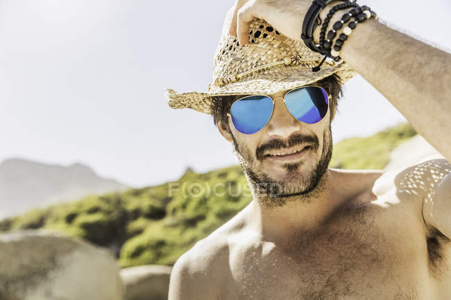 Portrait of man wearing blue mirrored sunglasses and straw hat on beach, Cape Town, South Africa — Stock Photo