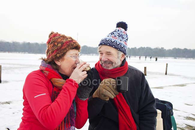 Пара пьет горячий напиток в снегу — стоковое фото