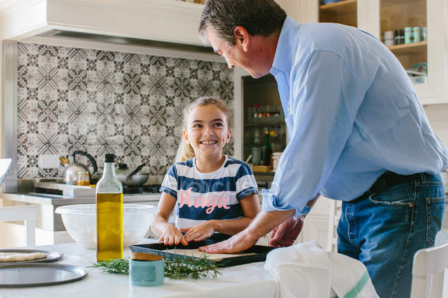 Grandfather and granddaughter preparing food — Stock Photo